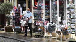 Seorang pemilik toko suvenir mengeluarkan barang dagangannya saat bisnis kembali buka di Windsor, barat London, Senin (12/4/2021). Inggris melonggarkan pembatasan terkait virus corona COVID-19. (Photo by Paul ELLIS/AFP)