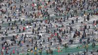 Peserta memancing ikan trout melalui lubang yang mereka buat di atas sungai beku di Hwacheon, Korea Selatan, Sabtu (5/1). Kontes ini merupakan bagian dari festival es tahunan yang menarik lebih dari satu juta pengunjung setiap tahun. (AP/Ahn Young-joon)