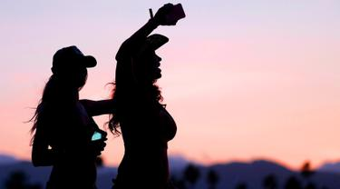 Dua wanita seksi bernyanyi dan berjoged menggunakan topi koboi saat menghadiri Festival musik Country Stagecoach di Empire Polo Club di Indio, California, 29 April 2016. (AFP PHOTO/Jason Kempin)