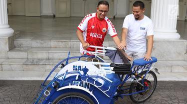 Gubernur DKI Anies Baswedan (kiri) menerima prototype becak listrik dari anggota DPR RI Hanafi Rais di Balai Kota DKI Jakarta, Minggu (11/3). Becak listrik tersebut dapat digunakan secara dikayuh atau menggunakan dinamo. (Liputan6.com/Immanuel Antonius)