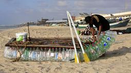 Nelayan Palestina, Mouad Abu Zeid memperbaiki perahunya yang terbuat dari botol plastik bekas di pantai Rafah, Jalur Gaza, 14 Agustus 2018. Zeid menyulap ratusan botol plastik bekas menjadi perahu untuk melaut demi menghidupi keluarganya (AFP/SAID KHATIB)