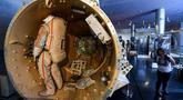 Seorang wanita melihat modul pintu air stasiun ruang angkasa Mir di Memorial Museum of Cosmonautics (atau Museum Peringatan Eksplorasi Luar Angkasa) di Moskow (20/8/2019). (AFP Photo/Kirill Kudryavtsev)