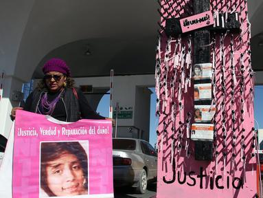 Aktivis membawa foto Jocelyn Calderon Reyes yang hilang pada 30 Desember 2013 di Jembatan Internasional Paso del Norte, Ciudad Juarez, Chihuahua, Meksiko, Rabu (7/3). Aksi ini menghormati Hari Wanita Internasional atau Women's Day. (HERIKA MARTINEZ/AFP)