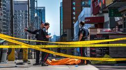 Petugas polisi berdiri dekat salah satu jasad akibat serangan mobil di Toronto bagian utara, Kanada, Senin (23/4). Serangan terjadi ketika sebuah van bergerak ke arah pejalan kaki di jalanan sibuk Toronto. (Aaron Vincent Elkaim/The Canadian Press via AP)