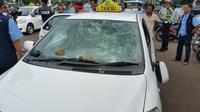 Kaca taksi rusak terkena lemparan batu (Liputan6.com/ Nanda Perdana Putra)