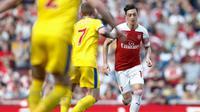 Aksi gelandang Arsenal, Mesut Ozil pada laga lanjutan Premier League yang berlangsung di Stadion Emirates, Minggu (21/4). Arsenal kalah 2-3 kontra Crystal Palace. (AFP/Adrian Dennis)