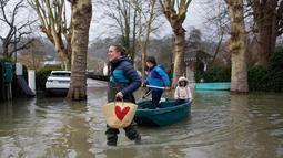 Seorang wanita menggunakan perahu membawa anak-anak di sebuah jalan banjir di Villennes sur Seine, sebelah barat Paris, (30/1). Sejumlah perjalanan kapal pesiar juga tergangu akibat hujan deras yang membuat sungai meluap. (AP Photo / Thibault Camus)