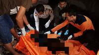 Petugas mengevakuasi korban kebakaran di Rokan Hulu yang hangus karena tidak bisa menyelamatkan diri. (Liputan6.com/M Syukur)