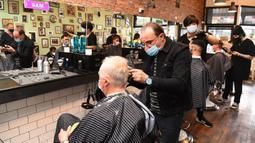 Para pria memotong rambut di barber shop di Melbourne, Australia, Senin (19/10/2020). Warga Kota Melbourne, pada Senin (19/10), akhirnya bisa bernafas lega saat sejumlah pembatasan dilonggarkan setelah menjalani lockdown tahap keempat yang ketat selama sekitar 100 hari. (William WEST/AFP)