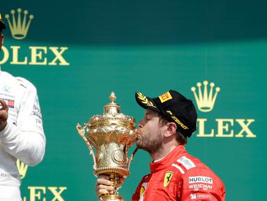 Pembalap Ferrari, Sebastian Vettel (benar) mencium piala di depan pembalap Mercedes, Lewis Hamilton (kiri) saat menjuarai F1 GP di Sirkuit Silverstone, Inggris, Minggu (8/7). Vettel mengungguli Lewis Hamilton dan Kimi Raikkonen. (AP Foto/Luca Bruno)