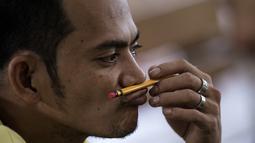 Narapidana memainkan pensilnya setelah mengikuti Ujian Akreditasi Nasional dan Pemeriksaan Kesetaraan di Penjara Manila City, Filipina, Minggu (19/11). Sekitar 900 napi, kebanyakan kasus narkoba, berpartisipasi dalam ujian SD dan SMA. (NOEL CELIS/AFP)