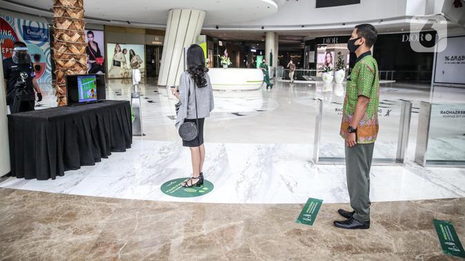 Karyawan antre mencoba alat pendeteksi suhu tubuh di Mal Central Park, Jakarta, Rabu (3/6/2020). Selain menerapkan protokol kesehatan ketat, pusat perbelanjaan juga menyediakan fasilitas pendukung 'physical distancing' sebagai persiapan operasional di era normal baru. (Liputan6.com/Faizal Fanani)