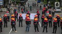 Massa aksi yang tergabung dalam Serikat Pekerja Indonesia (KSPI) membawa spanduk dan poster saat unjuk rasa di kawasan Patung Kuda, Jakarta, Rabu (16/12/2020). (Liputan6.com/Faizal Fanani)