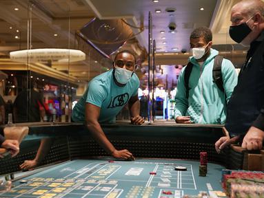 Pengunjung bermain dadu saat pembukaan kembali hotel dan kasino Bellagio di Las Vegas, Nevada, Amerika Serikat, Kamis (4/6/2020). Kasino di Nevada diizinkan kembali beroperasi setelah penutupan sementara untuk mencegah penyebaran virus corona COVID-19. (AP Photo/John Locher)