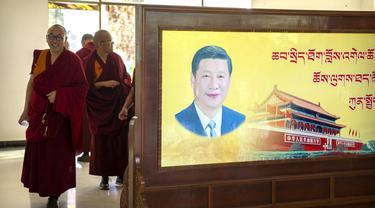 Para biksu berjalan melewati poster dengan potret Presiden China Xi Jinping dan Gerbang Tiananmen di Tibetan Buddhist College dekat Lhasa di Daerah Otonomi Tibet China barat, Senin, 31 Mei 2021 (AP)