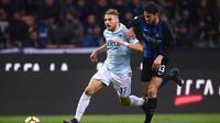 Striker Lazio, Ciro Immobile (kiri), mendapat pengawalan dari bek Inter Milan, Andrea Ranocchia, pada laga Serie A di Giuseppe Meazza, Milan, Sabtu (30/12/2017). (AFP/Marco Bertorello)