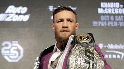 Petarung MMA Conor McGregor berpose dengan memperlihatkan dua sabuk miliknya jelang konferensi pers di New York, AS (20/9). McGregor akan melawan Khabib Nurmagomedov di UFC setelah absen selama dua tahun. (AP Photo/Seth Wenig)