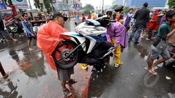 Pengendara motor berusaha menghidupkan motornya yang mati akibat menerjang banjir, Jakarta, Senin (6/2/2015).  Hujan yang turun sejak malam hingga kini membuat sejumlah ruas jalan tergenang air. (Liputan6.com/Faizal Fanani)