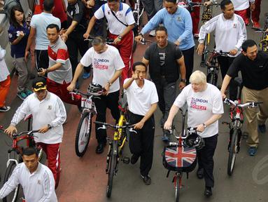 Presiden Joko Widodo (menunjuk) bersepeda bersama Walikota London, Boris Johnson di Jakarta, Minggu (30/11/2014). (Liputan6.com/Faizal Fanani)