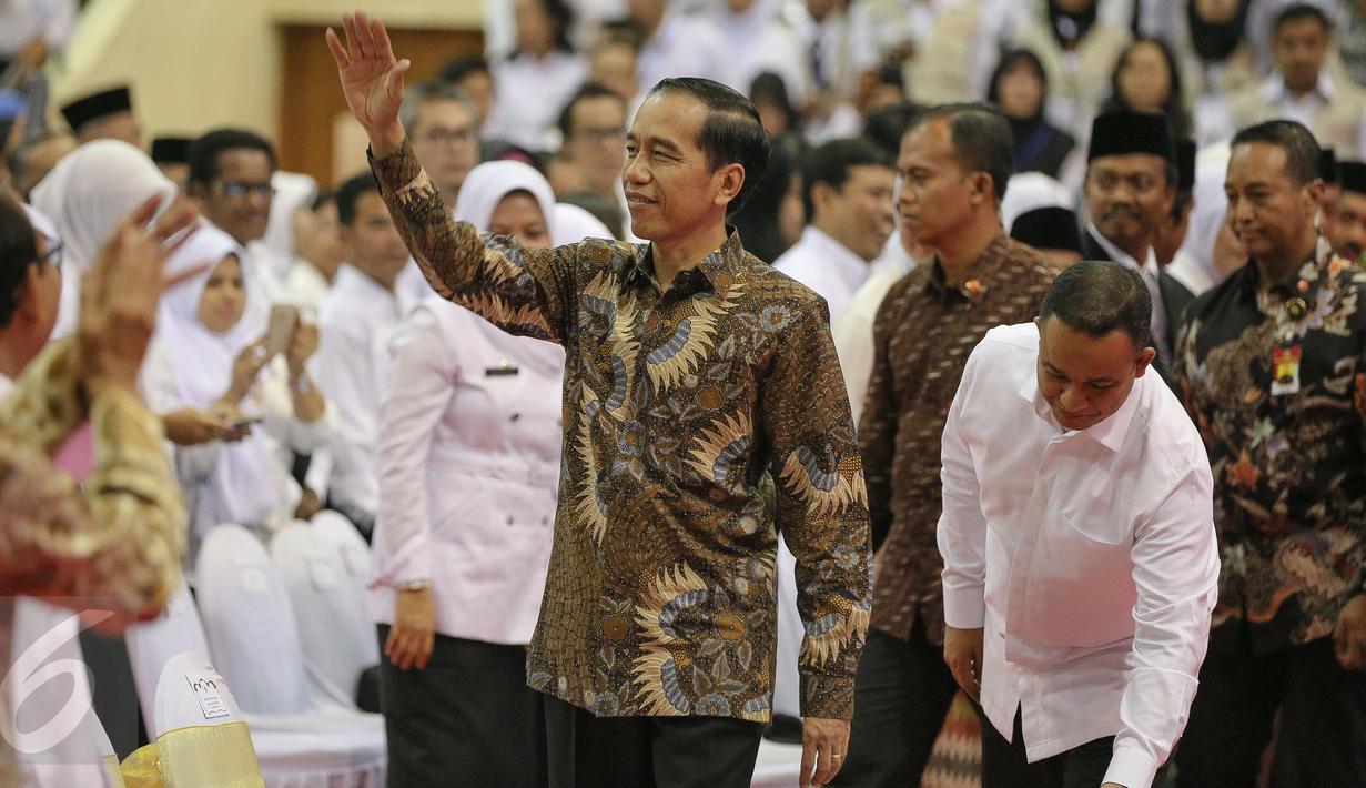 Presiden Joko Widodo (Jokowi) melambaikan tangan saat hadir dalam Peringatan Hari Guru Nasional 2015, Istora Senayan, Jakarta, Selasa (24/11). Peringatan hari guru tahun ini mengangkat tema 'Guru Mulia Karena Karya'. (Liputan6.com/Faizal Fanani)