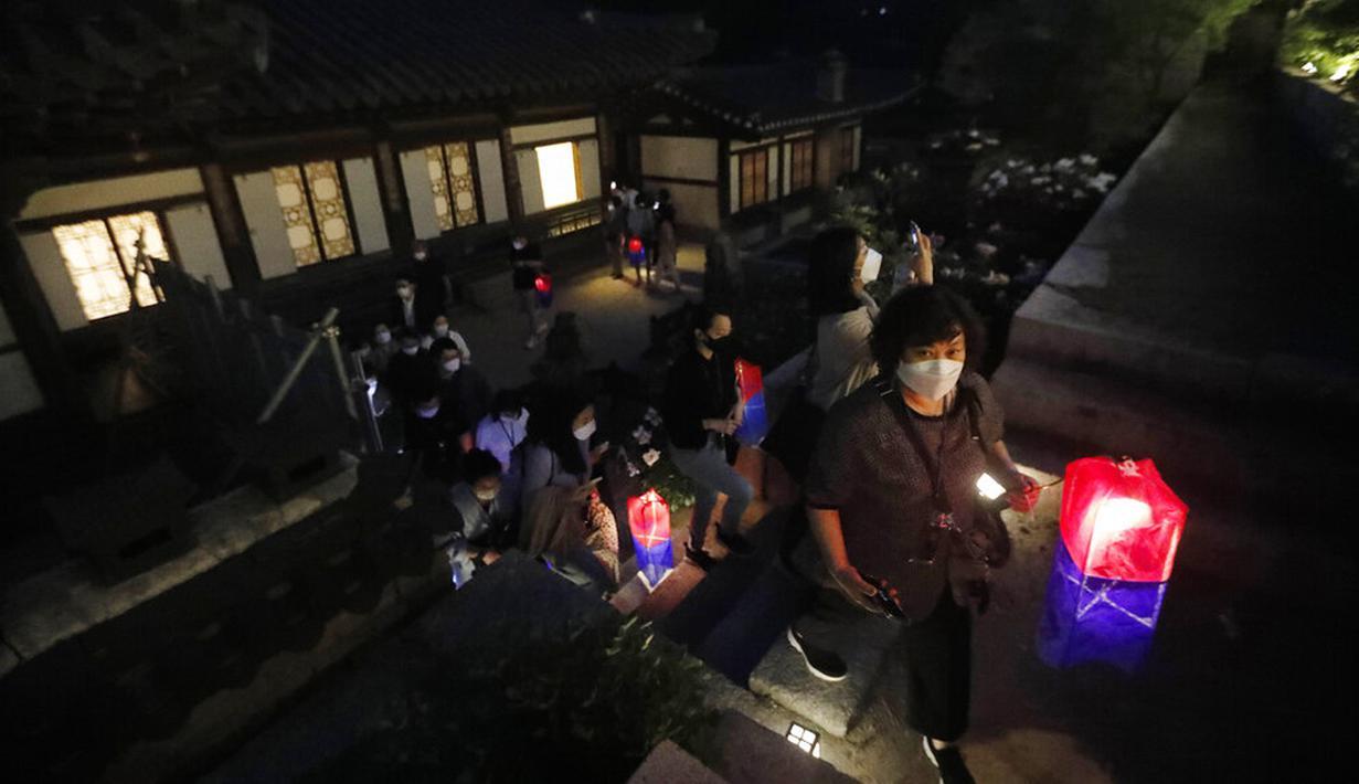 Pengunjung yang memegang lentera tradisional Korea berjalan-jalan selama Tur Cahaya Bulan di tengah pandemi virus corona COVID-19 di Istana Changdeokgung, Seoul, Korea Selatan, Kamis (13/5/2021). Istana Changdeok adalah istana Dinasti Joseon. (AP Photo/Ahn Young-joon)