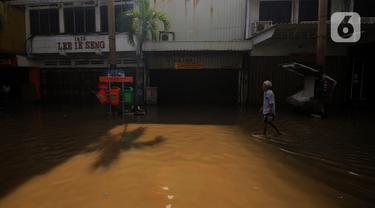 Warga melintas di depan pertokoan yang ada di kawasan Pasar Baru, Jakarta, Kamis (2/1/2020). Pasca banjir yang melanda sejumlah titik di Jakarta pada Rabu (1/1), aktivitas perniagaan di kawasan Pasar Baru masih terlihat sepi dan sebagian toko masih tutup. (Liputan6.com/Helmi Fithriansyah)