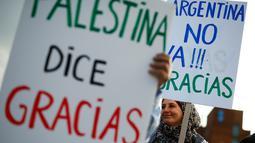 Aktivis pro-Palestina menunjukkan poster ungkapan terima kasih kepada timnas sepak bola Argentina di Barcelona (6/6). Selain aktivis ini, para pejabat sepak bola Palestina memuji Argentina dan bintangnya, Lionel Messi. (AFP Photo/Pau Barrena)