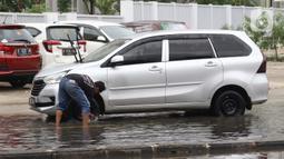 Pengendara memanfaatkan genangan air untuk mencuci kendaraan di Jalan HBR Motik Kemayoran, Jakarta, Selasa (25/2/2020). Hujan yang mengguyur Jakarta sejak Senin (24/2) malam membuat sejumlah kali meluap dan menyebabkan banjir. (Liputan6.com/Helmi Fithriansyah)