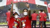 Kiper merangkap kapten Persija Jakarta, Andritany Ardhiyasa (kanan) bersama Ramdani Lestaluhu melakukan selebrasi usai menjuarai Piala Menpora 2021 di Stadion Manahan, Solo, Minggu (25/4/2021). (Bola.com/M Iqbal Ichsan)