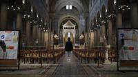 Seorang jemaah berdoa saat stiker jaga jarak sosial terpasang di kursi setelah kebaktian Kamis Putih di Gereja Saint Pierre de Montrouge, Paris, Prancis, Kamis (1/4/2021). Prancis bersiap melakukan lockdown setelah pemerintah menemukan adanya lonjakan kasus COVID-19. (AP Photo/Francois Mori)