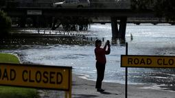 Seorang wanita mengambil gambar banjir yang melanda Kota Forbes, kawasan pedalaman di New South Wales, Australia, Selasa (27/9). Lebih dari 100 rumah dan lahan tanaman rusak parah akibat banjir ini. (REUTERS / Jason Reed)