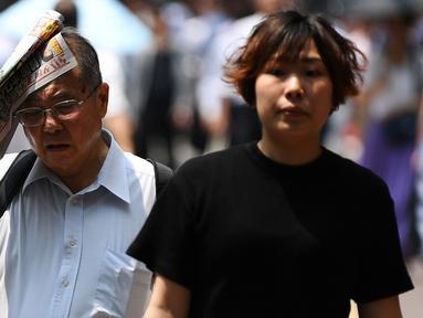Seorang pria melindungi dirinya dari sinar matahari dengan sebuah koran saat gelombang panas di Tokyo, Jepang (1/7/2019). Cuaca panas ekstrem yang melanda Jepang telah menewaskan puluhan orang tewas dan menyebabkan ribuan orang masuk rumah sakit dengan gejala dehidrasi. (AFP Photo/Charly Triballeau)