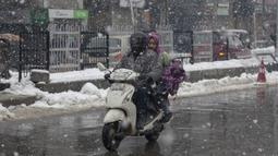 Seorang pria Kashmir mengendarai skuter saat salju turun di Srinagar, Kashmir yang dikuasai India (15/1/2020). Selama dua hari terakhir wilayah Himalaya telah menyaksikan hujan salju lebat yang mengakibatkan serangkaian longsoran dan tanah longsor. (AP Photo/Dar Yasin)