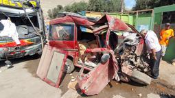 Seorang pria mengamati kondisi sebuah minivan yang ditabrak bus tingkat di daerah Arequipa, Peru, Senin (6/1/2020). Saat ini pihak operator bus masih melakukan investigasi terhadap kecelakaan maut itu. (Photo by Javier Casimiro / AFP)