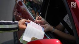 Polisi memberikan surat tilang kepada mobil berplat nomor genap di persimpangan Jalan Dharmawangsa X dan Jalan Fatmawati, Jakarta, Senin (9/9/2019). Perluasan wilayah ganjil genap berlaku mulai hari ini dan terbagi di beberapa titik, salah satunya Jakarta Selatan. (Liputan6.com/Immanuel Antonius)