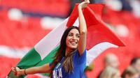 Suporter Timnas Italia mengibarkan bendera saat menyaksikan pertandingan melawan Spanyol pada laga semifinal Euro 2020 di Stadion Wembley, Rabu (7/7/2021). (Foto:AFP/Carl Recine,Pool)