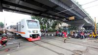 Kereta melintas di perlintasan kereta api di kawasan Roxy, Jakarta, Rabu (21/3). Petugas Sudinhub Jakpus telah menutup akses perlintasan KA di depan Roxy 20 September 2017, namun mendapat protes keras dari warga.  (Liputan6.com/Arya Manggala)