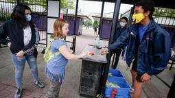 Petugas membagikan masker gratis kepada pengunjung di pintu masuk Playland Amusement Park, di Vancouver, British Columbia, Kanada, pada 10 Juli 2020. Playland Amusement Park dibuka kembali untuk umum pada Jumat (10/7), dengan langkah-langkah protokol kesehatan. (Xihua/Liang Sen)