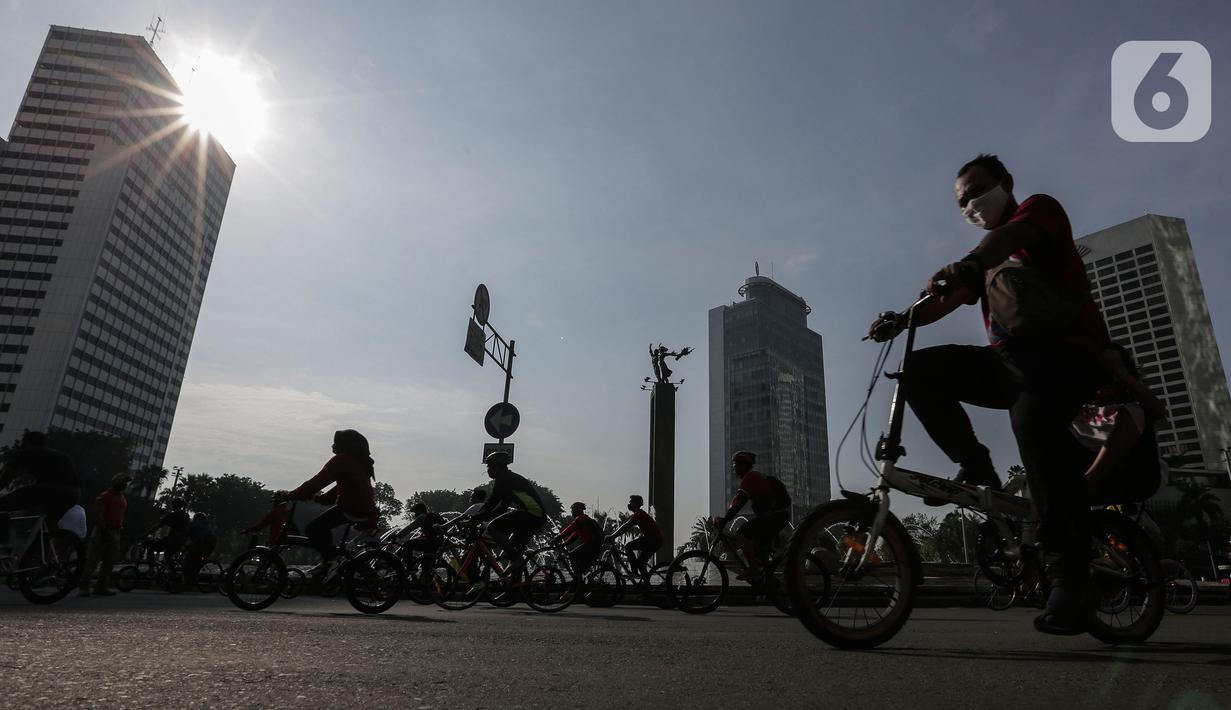 Warga berolahraga di area Car Free Day (CFD) kawasan MH Thamrin, Jakarta, Minggu (21/6/2020). Hari ini adalah kali pertama digelarnya CFD Jakarta di sepanjang Jalan Sudirman - Thmarin saat Pembatasan Sosial Berskala Besar (PSBB) Masa Transisi. (Liputan6.com/Johan Tallo)