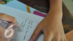 Seorang siswa menulis surat untuk Presiden RI Joko Widodo di SDN Sukasari 4 Kota Tangerang, Selasa, (29/16). Isi Surat tersebut meminta kepada Jokowi agar prihatin dengan keberadaan generasi muda Indonesia. (Liputan6.com/Faisal R Syam)