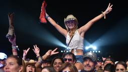 Seorang pengunjung wanita tersenyum saat berjoged menggunakan topi koboi saat menghadiri Festival musik Country Stagecoach di Empire Polo Club di Indio, California, 29 April 2016. (AFP PHOTO/Kevin Winter)