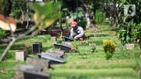 Petugas merawat makam di Tempat Pemakaman Umum (TPU) Karet Bivak, Jakarta, Selasa (11/5/2021). Pemprov DKI akan memberlakukan larangan ziarah kubur Idulfitri di seluruh TPU mulai 12 hingga 16 Mei untuk mencegah terjadinya penyebaran Covid-19 saat berkumpul untuk berziarah. (Liputan6.com/JohanTallo)