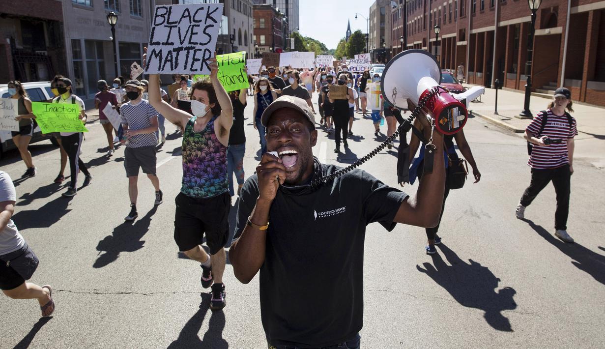 Chadwick Workman memimpin nyanyian ketika pengunjuk rasa memprotes kematian George Floyd di Springfield, Illinois, Amerika Serikat, Minggu (7/6/2020). Gelombang protes atas kematian George Floyd terus mengguncang Amerika Serikat. (Ted Schurter/The State Journal-Register via AP)