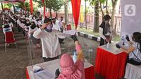 Peserta memberikan berkas sebelum mengikuti proses Tes Standar Kompetensi Dasar (SKD) CPNS di BKN, Jakarta, Kamis (2/9/2021). Sebanyak 800 peserta mengikuti tes yang dibagi dua sesi dan menerapkan protokol kesehatan yang ketat. (Liputan6.com/Herman Zakharia)