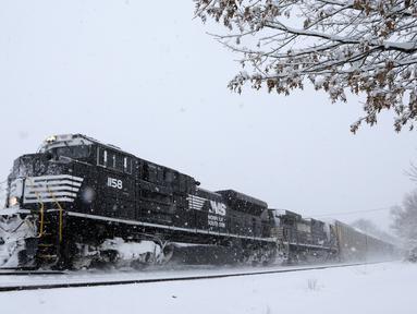 Sebuah kereta barang melaju saat badai salju di Manville, New Jersey (21/3). Badai salju yang melanda sebagian Amerika Serikat telah membawa salju dan angin kencang. (AP/Julio Cortez)