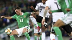 Gelandang Irlandia Utara, Corry Evans, berebut bola dengan gelandang Jerman, Serge Gnabry, pada laga Kualifikasi Piala Eropa 2020 di Windsor Park, Belfast, Senin (9/9). Irlandia Utara kalah 0-2 dari Jerman. (AFP/Paul Faith)