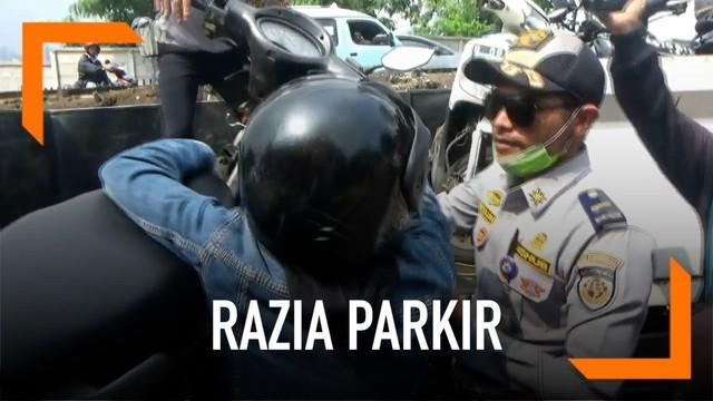 Razia parkir sembarangan dilakukan oleh petugas Dishub DKI. Seorang tukang ojek marah ketika sepeda motornya di angkut kena razia.