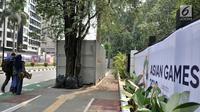 Pengendara sepeda melintas dekat kontainer tiket Asian Games 2018 yang berdiri di sepanjang trotoar Jalan Pintu 1 Senayan, Jakarta, Selasa (7/8). (Merdeka.com/Iqbal Nugroho)