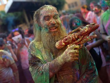Seorang pria dengan tubuh penuh cat memegang pistol plastik saat mengikuti Festival Monsoon Holi di Madrid, Spanyol (5/8). Festival yang menjadi salah satu tradisi di India dan Nepal ini, kini menjadi trend di sejumlah negara. (AP Photo/Francisco Seco)