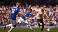 Gelandang Manchester United, Nemanja Matic, berusaha melewati pemain Everton pada laga Premier League di Goodison Park, Minggu (21/4). Everton menang 4-0 atas Manchester United. (AFP/Oli Scarff)
